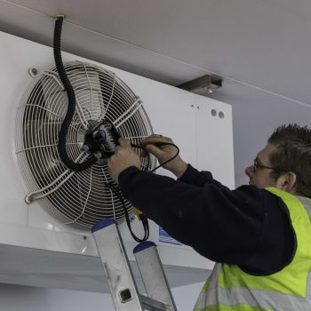An engineer replacing a fan on a refrigeration unit